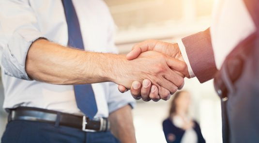 Businessmen shaking hands during a meeting. Closeup of business handshake between two colleagues in a modern office. Successful businessmen handshaking closing a deal. Agreement and business concept.
